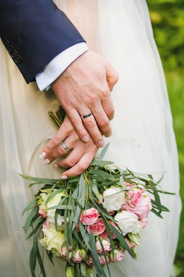 Young couple after wedding in Church, their hands close up. Wedding of young people, the bride holds a beautiful bouquet with royalty free stock photography