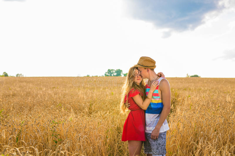 Young couple in the wheat field. Summer or autumn season, copy space. Rear view of young couple in the wheat field. Summer or autumn season, copy space royalty free stock photography