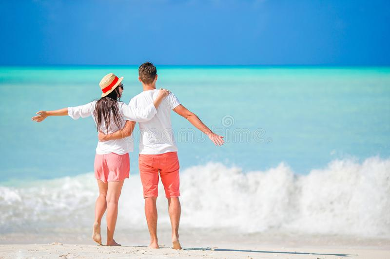 Young couple on white beach. Happy family on honeymoon vacation stock photo