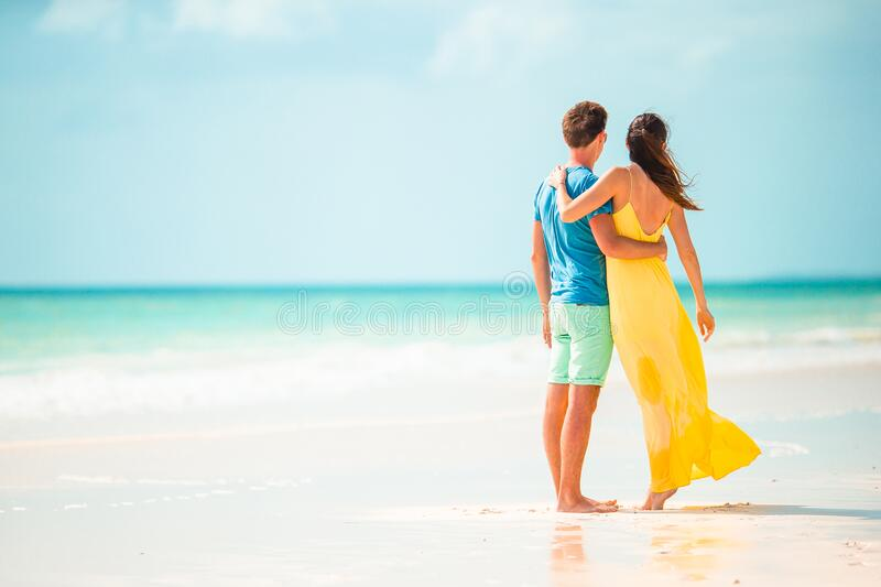 Young couple on white beach during summer vacation. Happy family enjoy their honeymoon. Young couple on white beach during summer vacation. Family of two on the stock photo