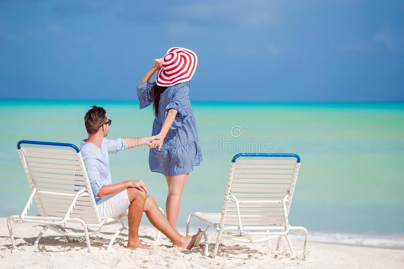 Young couple on white beach during summer vacation. Happy family enjoy their honeymoon stock image