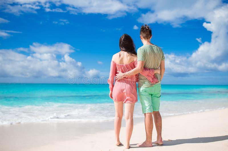 Young couple on white beach during summer vacation. Happy family enjoy their honeymoon. Young couple on white beach during summer vacation. Family of two on the stock images
