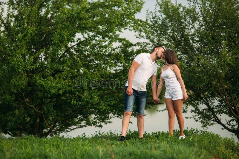 Young couple in white stand on the hill. Background of trees and lake royalty free stock image
