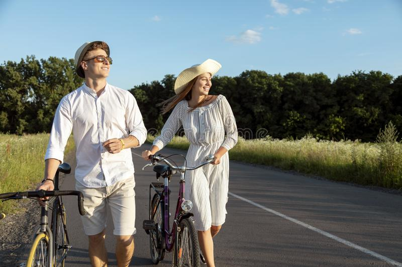 Young Couple Wheeling Bicycles Along Rural Road royalty free stock photo