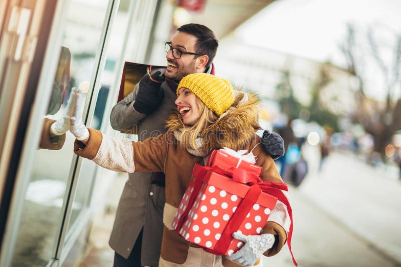 Couple window shopping on a winter day, looking for a Christmas gifts stock images