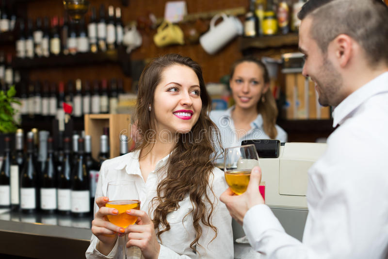 Young couple with wine at bar. Smiling bartender and young guests couple with wine at bar counter. Focus on girl stock photography