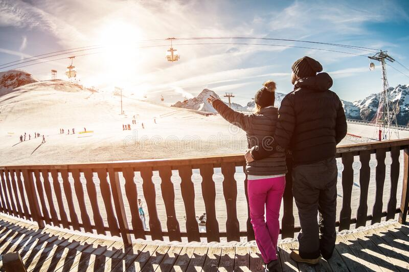 Young couple in winter vacation at snow resort mountain - Skiers tourists relaxing in ski slope chalet - Travel, holiday, stock photography