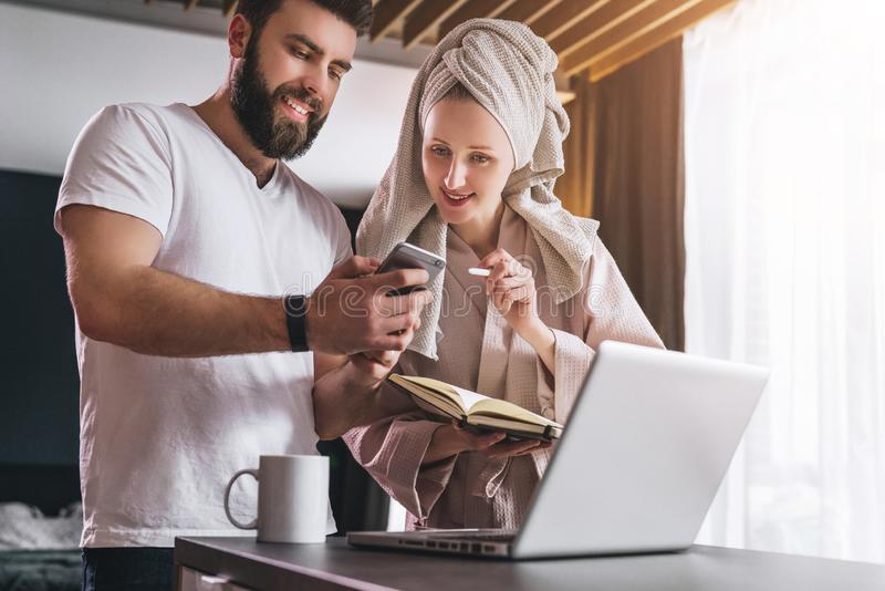 Young couple, woman in bathrobe and towel on her head, stands in kitchen near table with laptop. Freelancers work home. Young couple, women in bathrobe and stock image