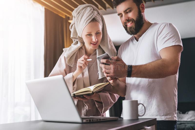 Young couple, woman in bathrobe and towel on her head, stands in kitchen near table with laptop. Freelancers work home. Young couple, women in bathrobe and royalty free stock photography