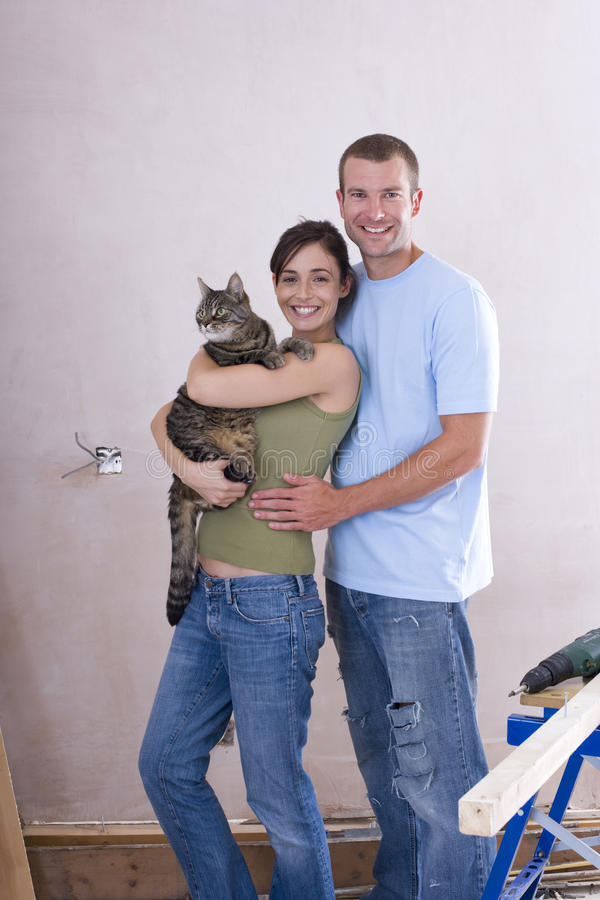 Young couple, woman with cat, smiling, portrait royalty free stock photography