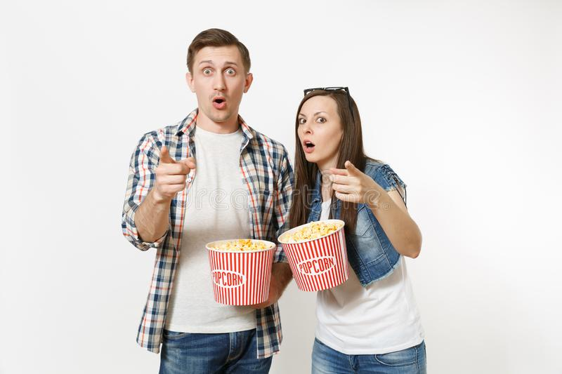 Young couple, woman and man in 3d glasses and casual clothes watching movie film on date, holding buckets of popcorn royalty free stock images