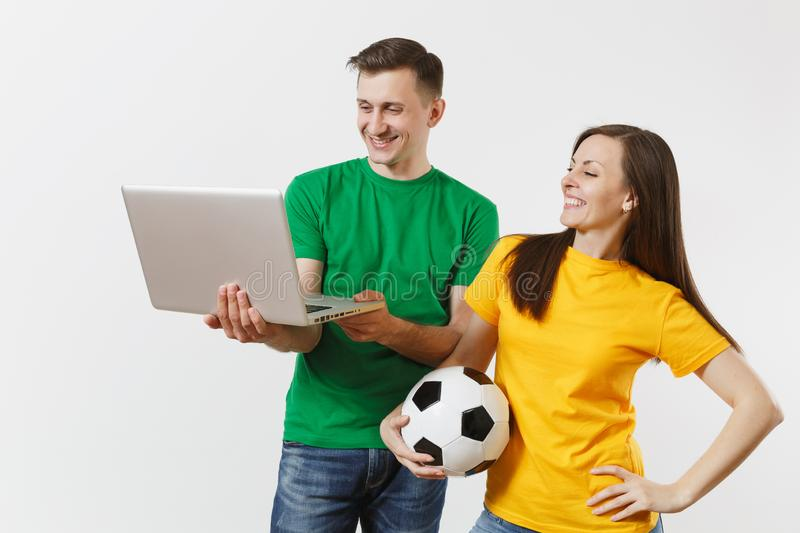 Young couple, woman man, football fans in yellow green t-shirt cheer up support team with soccer ball, watching game on royalty free stock photos