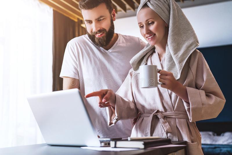 Couple, woman in bathrobe standing in kitchen, drinking coffee and using a laptop.Girl and guy watch news on computer. Young couple, women in bathrobe standing stock images