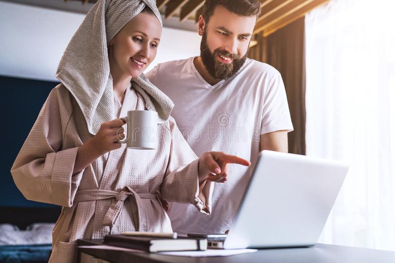 Couple, woman in bathrobe standing in kitchen, drinking coffee and using a laptop.Girl and guy watch news on computer. Young couple, women in bathrobe standing royalty free stock images