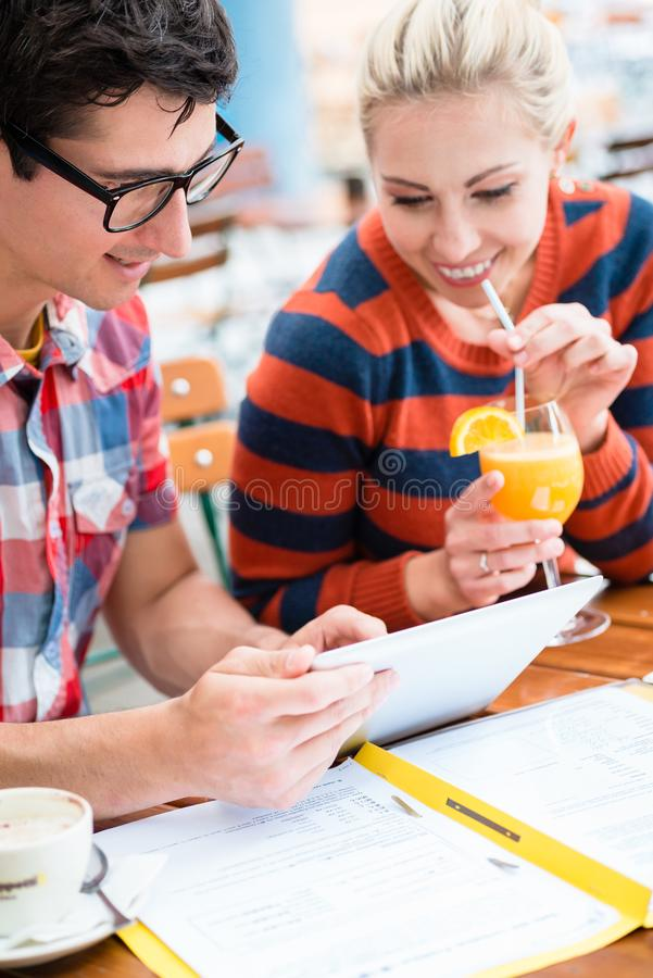 Couple in street cafe watching pictures of holidays. Young couple, women and man, in street cafe drinking coffee and juice while watching pictures of holidays stock photo