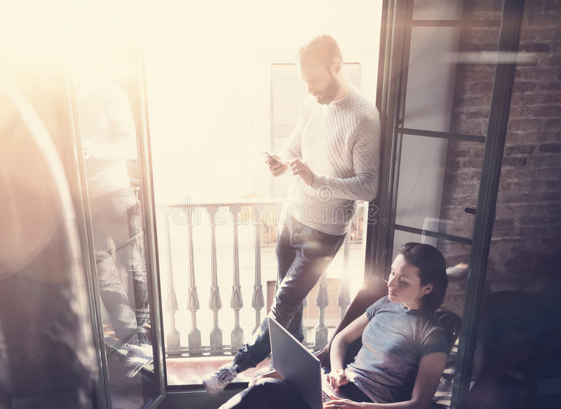 Young couple work together. Photo woman and bearded man working with new startup project in modern loft. Using royalty free stock image