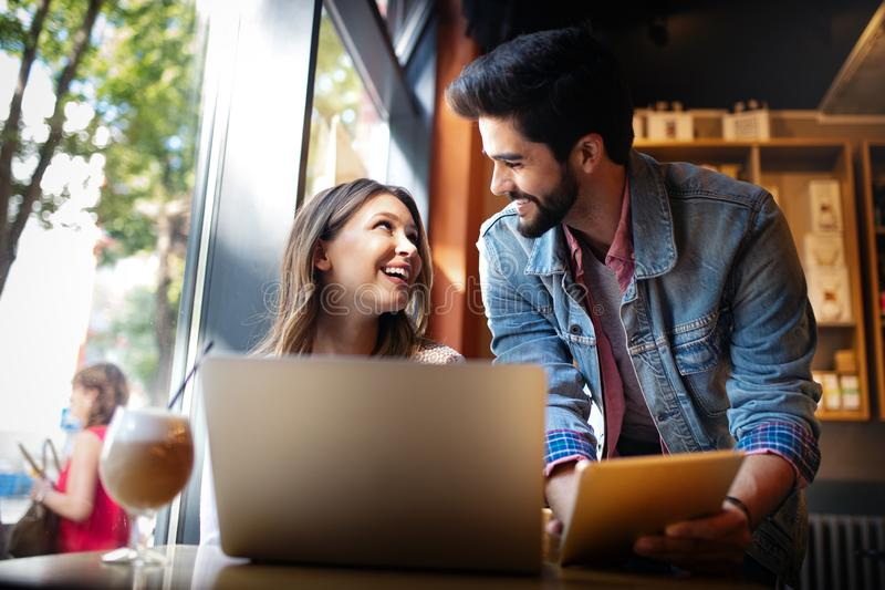 Young couple is working in cafe on laptop and smiling. stock photography