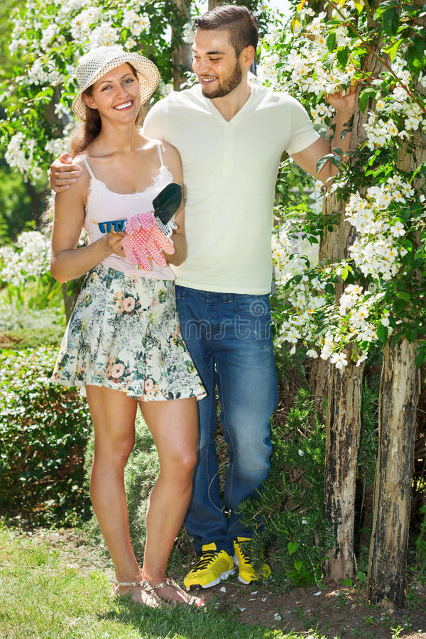 Young couple working in garden. Young happy couple working in the flower garden stock image