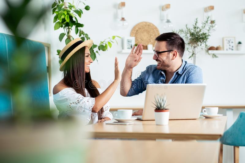 Young couple is working in cafe on laptop and smiling. - Image stock photos