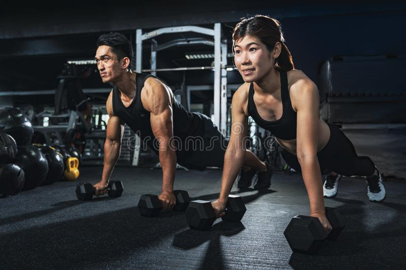 Young couple is working out at gym. Attractive woman and handsome muscular man are training in light modern gym. Doing plank on ke royalty free stock photography