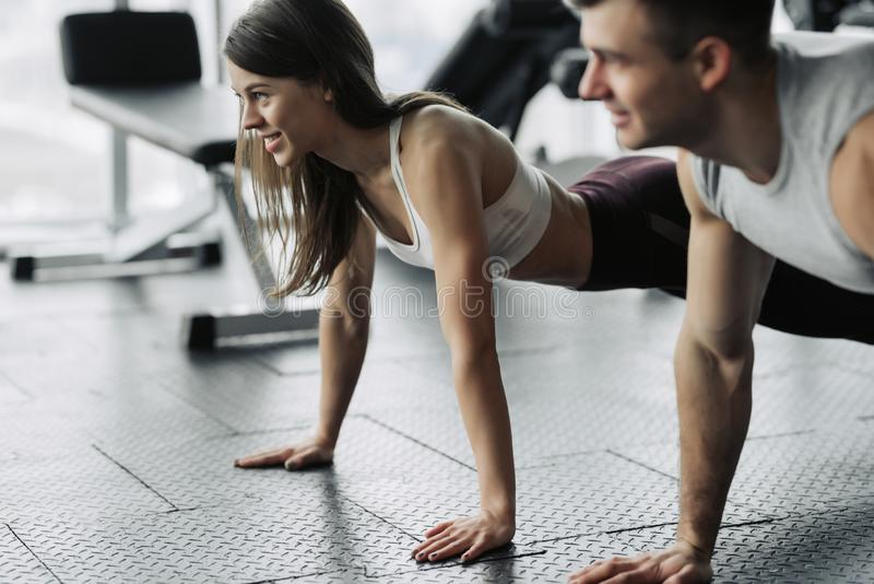 Young couple is working out at gym. Attractive woman and handsome muscular man are training in light modern gym. Doing plank.Push- royalty free stock images