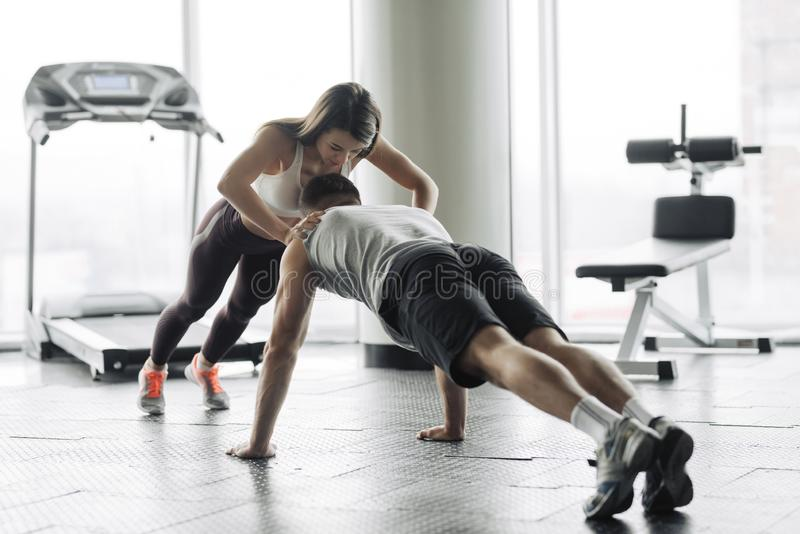 Young couple is working out at gym. Attractive woman and handsome muscular man are training in light modern gym. Double plank. Man royalty free stock photos