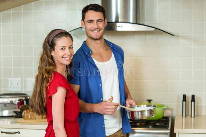 Young couple working together in kitchen royalty free stock images