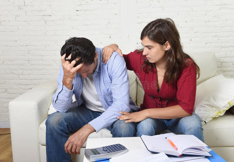 Young couple worried home in stress wife comforting husband accounting debt unpaid bills bank papers expenses royalty free stock image