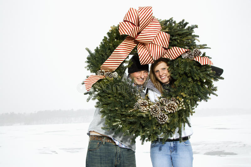 Young Couple with Wreath. Young adult couple in the winter holding a Christmas wreath. Their heads are framed by the wreath. Horizontal shot royalty free stock photography