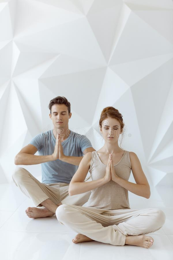 Young couple in yoga pose stock image