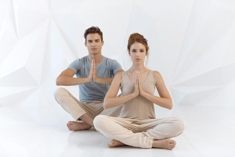 Young couple in yoga pose royalty free stock photos