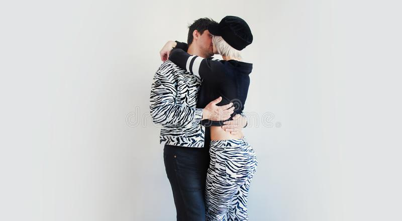 Couple in zebra pring clothes kissing on white background. stock images