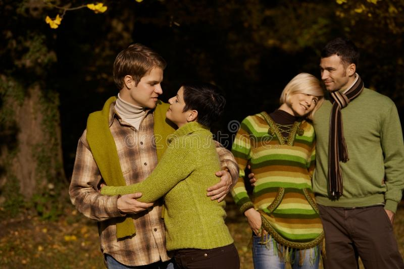 Young couples in autumn park. Smiling young couples standing in autumn park, embracing royalty free stock photo