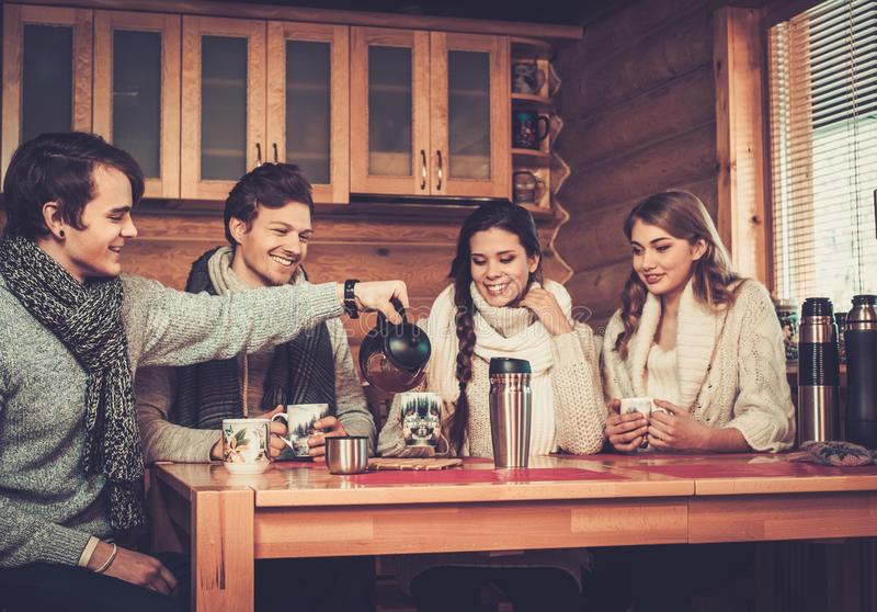 Young couples drinking hot tea in winter cottage. Kitchen stock photo