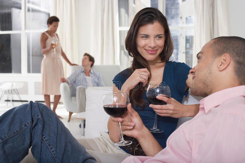 Young Couples Drinking Wine In Living Room stock images