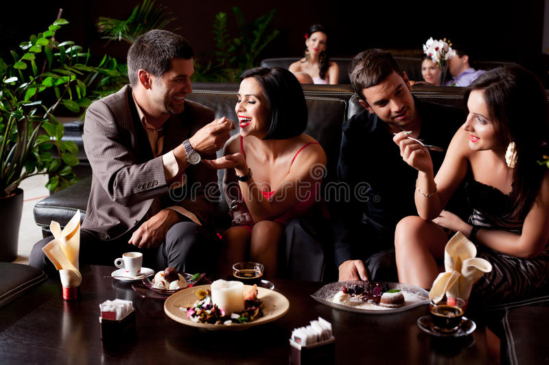 Young couples eating deserts royalty free stock photography