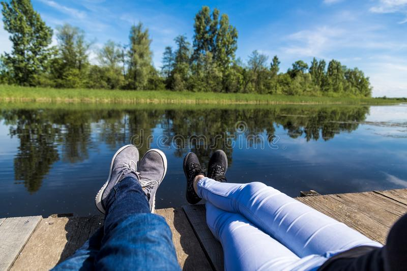 Young couples feet sitting on dock next to beautiful lake stock photo