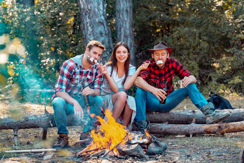 Young couples having picnic in woods. Young people having a camping. Company friends enjoy relaxing together in forest royalty free stock image