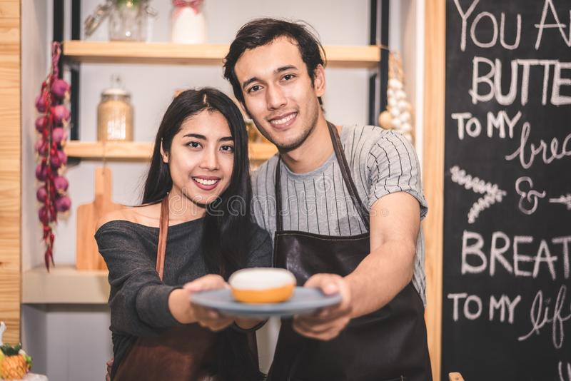Young couples making bakery donuts and bread at bakery shop as b. Usiness ownership entrepreneur. Husband and wife cooking together in kitchen. Happiness people royalty free stock image