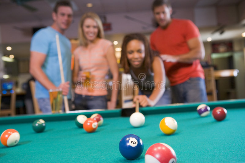 Young couples playing pool in a bar. (focus on pool table royalty free stock image