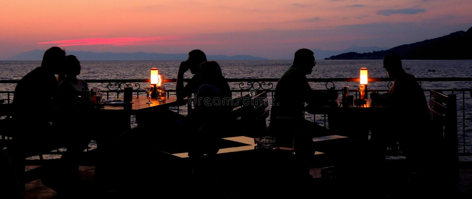 Young couples at restaurant having dinner. Silhouette. Young couple at restaurant having dinner near the sea with lamps on teir tables stock photography