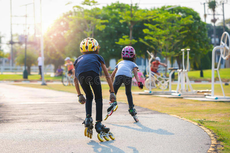 Young couples roller skates outdoor in park. Young couples roller skates outdoor in park stock photo