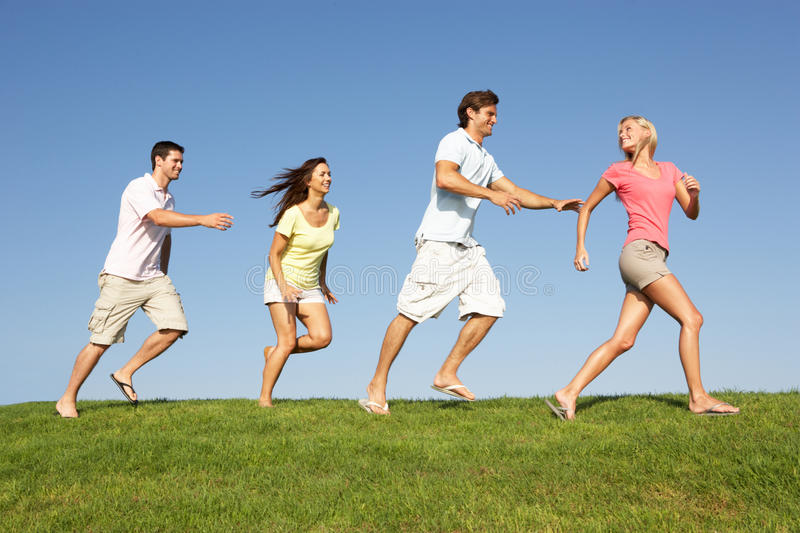 Download Young Couples Running Through Field Stock Photo - Image: 17058990
