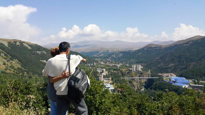 Young couples went to the tourist city of Jermuk, stand on the mountain and manually show each other what picturesque places stock photography