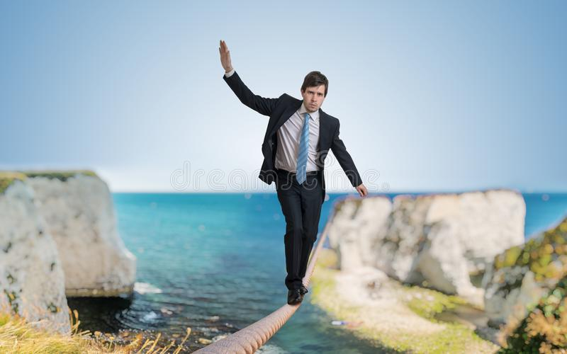 Young courageous businessman is walking on rope.  royalty free stock photo