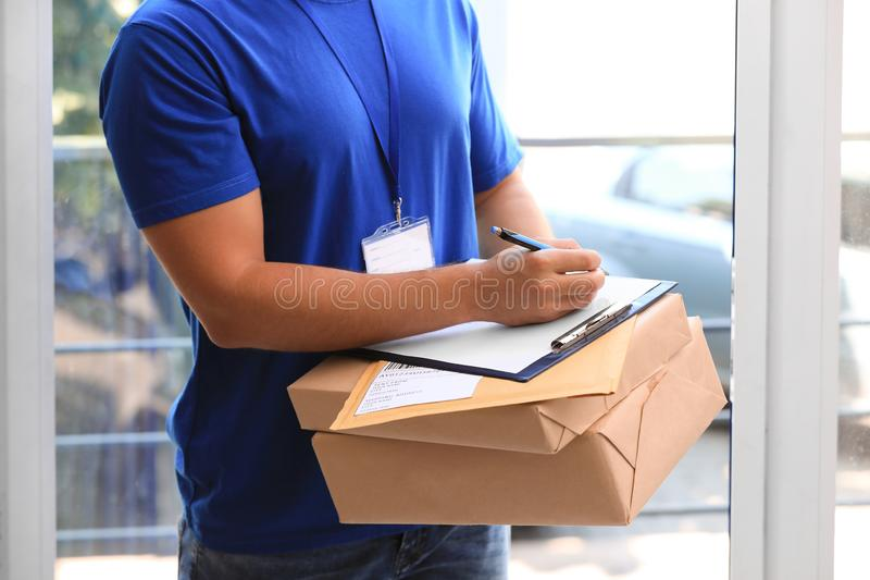 Young courier delivering parcels on doorstep. Closeup royalty free stock photos