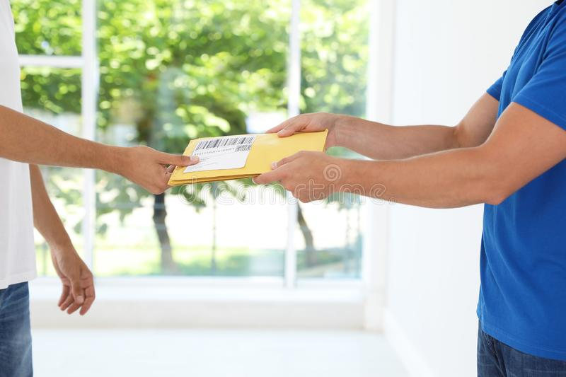 Young courier giving envelopes to client near window, closeup. Young courier giving envelopes to client near window indoors, closeup stock image