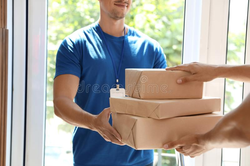 Young courier giving parcels to client in doorway. Closeup stock image