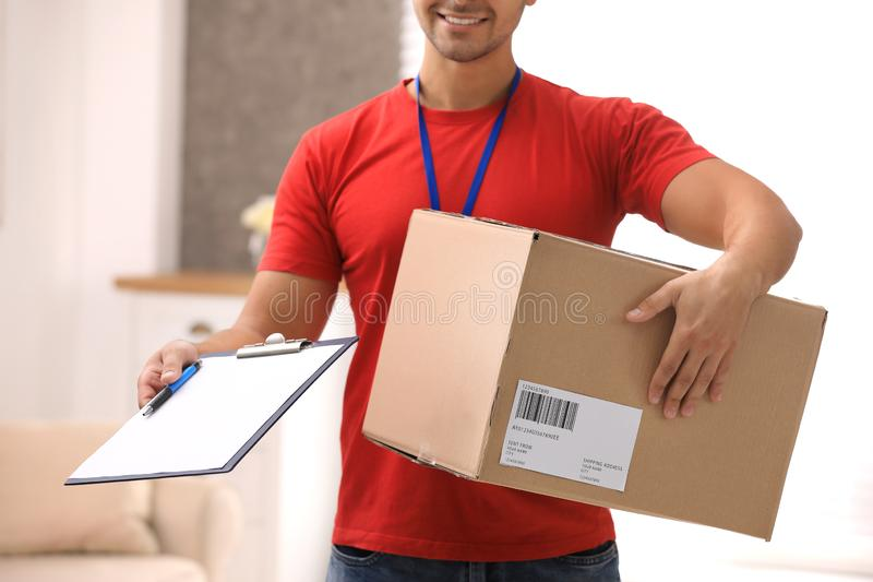 Young courier holding parcel and clipboard indoors. Delivery service. Young courier holding parcel and clipboard indoors, closeup. Delivery service stock images