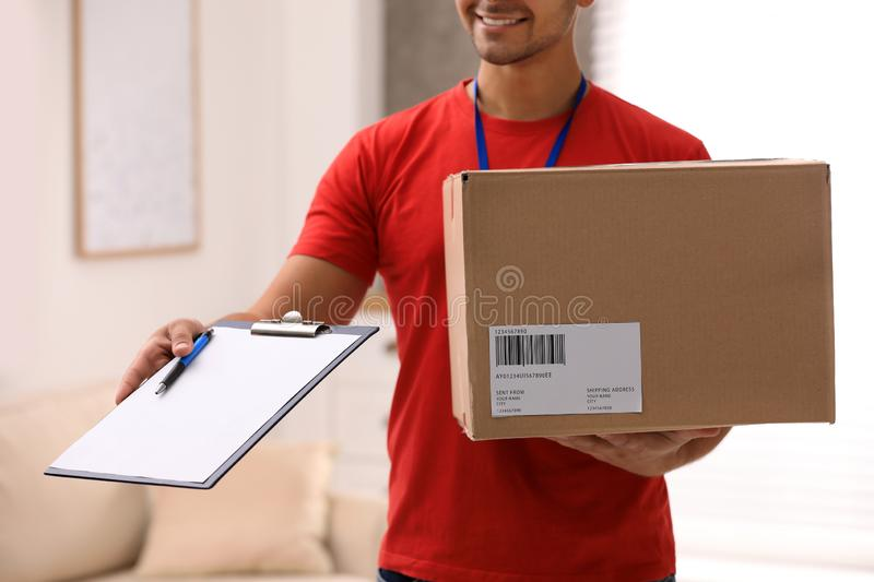 Young courier holding parcel and clipboard indoors. Delivery service. Young courier holding parcel and clipboard indoors, closeup. Delivery service royalty free stock photos